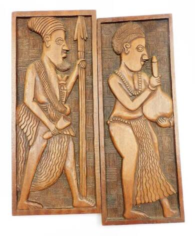 Two 20thC African tribal carved panels, the first figure in flowing robes holding vessel, the other figure holding spear, with plain borders, 51cm x 20cm.