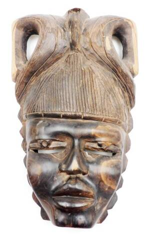 A heavily carved African tribal face mask, with elaborate hairstyle and pierced eyes, with shaped nose and lips, heavily carved, 39cm high.