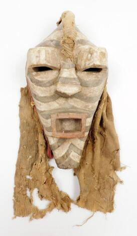 A heavily carved African tribal face mask, in black and white decoration with pierced raised eyes and other heavily carved features, with part cloth surround, 34cm high.