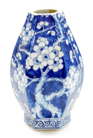 A Chinese porcelain baluster vase of octagonal section, profusely decorated with prunus flowers on a blue ground, four character Qianlong mark to base, probably early 20thC, neck reduced, 21cm high.