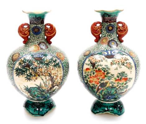 A pair Japanese Kutani pottery bulbous vases with compressed trumpet necks, decorated with panels of flowers within a scrolling karakusa (octopus tentacle) and flowerhead ground, on shaped feet, Meiji period, 29cm high. (2)