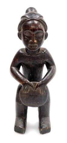 An African tribal carved figure, formed holding drum, with elaborate head dress, 34cm high.