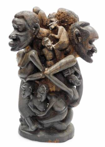A heavily carved African tribal group, formed as many entwined figures, on a shaped base, 39cm high.