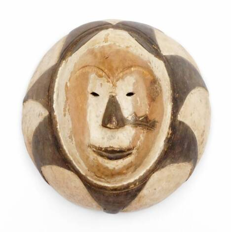 An African tribal face mask, with pierced eyes, partially decorated with an outer sun motif, 28cm wide.
