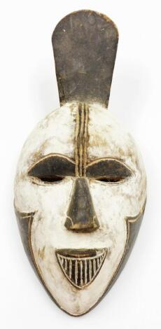 A heavily carved African tribal face mask, with pierced eyes and elaborate mouth, decorated in black and white, 38cm high.