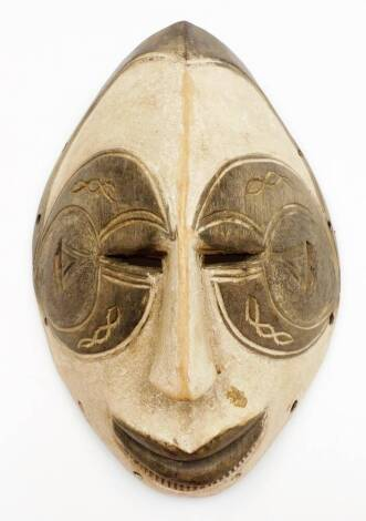 An African tribal face mask, of shaped ellipse form with pierced eyes, partially carved face and an arrangement of circular holes to the border, 31cm high.