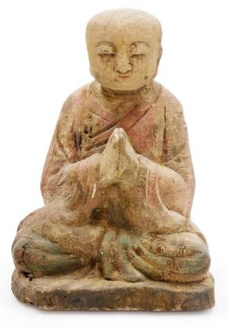 A Chinese carved wood statue of a monk, in flowing robes, at prayer in seated pose, possibly 18thC, 23cm high.