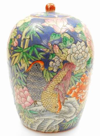 A Chinese famille rose ovoid jar and cover decorated with parakeets and chrysanthemums, bamboo etc on a blue ground, printed six character Qianlong mark to base, 20thC, 34cm high.