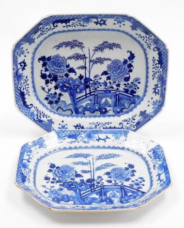 A duo of 18thC Chinese blue and white porcelain octagonal export meat plates, decorated with bamboo peony and other flowers beside a fence and flowers, shaped diaper and leaf borders, 46cm wide and 41cm wide.