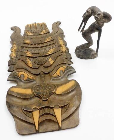 A heavily carved African tribal wooden figure group, 23cm high, and a carved Eastern wall mask. (2)