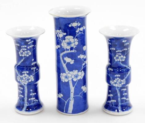 A Chinese porcelain prunus vase trio, comprising two gu shaped vases and a cylinder vase of trumpet form, decorated with prunus flowers on a blue ground, four character Kangxi marks to base of two,19thC, 19cm high.