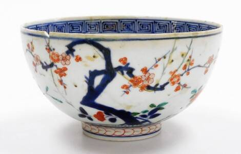 A Japanese Imari porcelain bowl, with an inner Greek keyfret border with peony to the centre, centred by a flower, the exterior with prunus branches, the base with stylized chrysanthemum head marked, 18thC, 18cm diameter. (AF)
