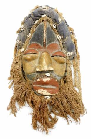 A heavily carved African tribal head, with hair and beard picked out with shells, with pierced eyes, partially painted red and black, main body, 39cm high.