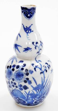 A Chinese porcelain blue and white double gourd vase, decorated with a butterfly above flowers, four character Kangxi mark, 19thC, 21cm high.
