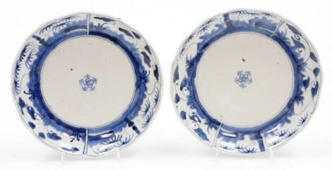 A pair of Japanese porcelain blue and white plates, with central floral emblems and outer panels of bamboo and lotus, the reverse with Fuki Choshun mark, 19thC,18cm wide. (AF)