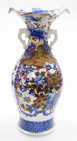 A Japanese porcelain blue and white vase, with flared neck and ear handles decorated with flowers and birds, applied with later decoration in lacquer of ho-o bird and peonies, three character mark beneath, Meiji period. 54cm high. (AF)