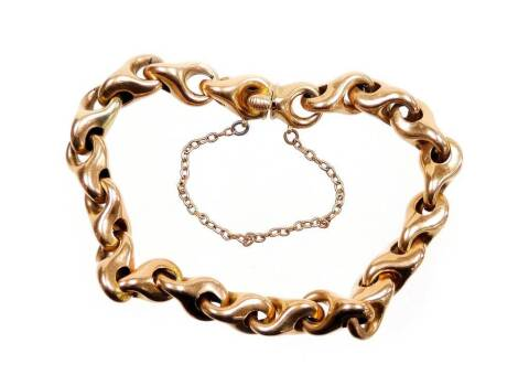 A gate bracelet, with hoop and loop elongated links, slide in clasp and safety chain, yellow metal, stamped 10, 16cm long overall, 12.3g all in. (AF)