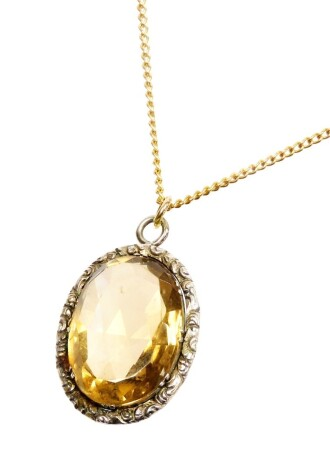 A silver framed citrine pendant and chain, the oval pendant in a florally engraved oval silver frame, 3cm x 2.5cm, on a gold plated chain.