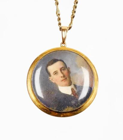 A Victorian portrait pendant and chain, the circular portrait depicting a gentleman in suit, unsigned, in a yellow metal frame bearing the initials AHL?, marked 10ct, 4cm diameter, on a gold plated chain.