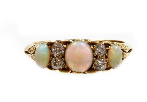 An 18ct gold opal and diamond dress ring, set with three oval opals and four tiny diamonds, in scroll carved raised ring head, ring size M½, 4.1g all in.