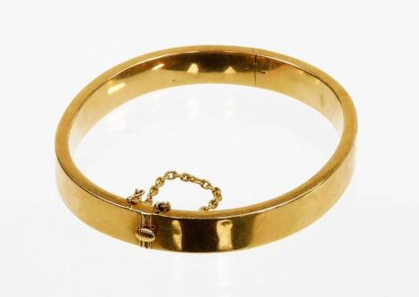 A hinged bangle, of plain design, with safety chain, yellow metal, marked 15ct to clasp, 5.5cm diameter, 14.9g all in.