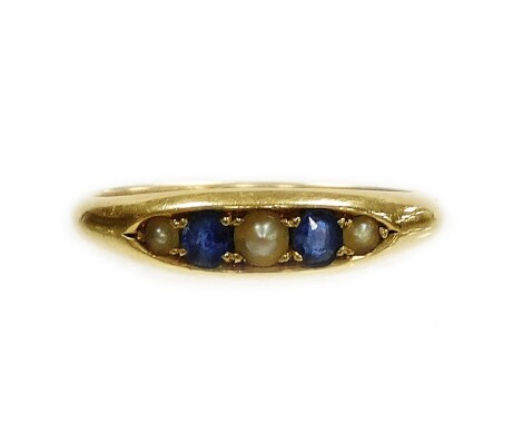 An 18ct gold sapphire and seed pearl marquise ring, set with two round brilliant cut sapphires and three seed pearls, ring size O, 3.3g all in.