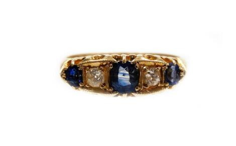 A Victorian 18ct gold sapphire and diamond ring, set with three oval cut sapphires, each in claw setting and two round brilliant cut diamonds, in a boxed Deco type frame surround, with fanned shoulders, ring size O, 4g all in.