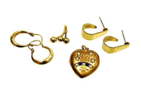 A group of earrings and other jewellery, comprising a pair of 9ct gold hoops, 1.1g, a pair of gold plated hoops, three 9ct gold studs, lacking backs, 0.4g, and a gilt metal locket, set with blue paste and seed pearls. (6)