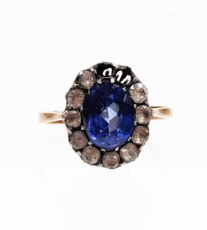 An Edwardian style dress ring, with synthetic sapphire and paste stones arranged in a floral cluster, size M, two white paste stones lacking, on a yellow metal band, unmarked, 3g all in.