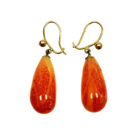 A pair of orange hardstone drop earrings, each on a yellow metal wire frame, unmarked, 5.6g all in.