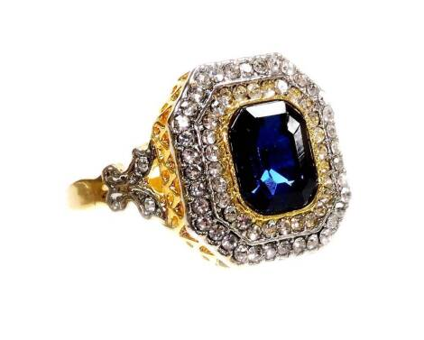 An Art Deco style modern dress ring, set with blue and white paste stones, on modern costume band, ring size X.