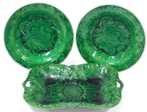 A late 19thC green glazed Majolica leaf dish, of shaped rectangular form, with moulded handles and floral decoration, unmarked, 29cm wide, and two further green leaf dish Majolica soup bowls, unmarked. (3)