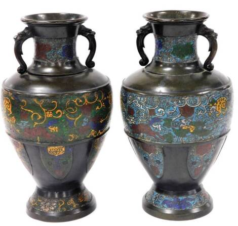 A matched pair of late 19thC/early 20thC champleve bronze urnular vases, with dragon handles and bodies decorated with varying colours, on circular feet 39cm high. (2)