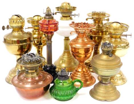 Various brass and other lamp bases, one with red moulded glass reservoir and reeded stem, 33cm high, other brass lamp bases, etc. (a quantity)