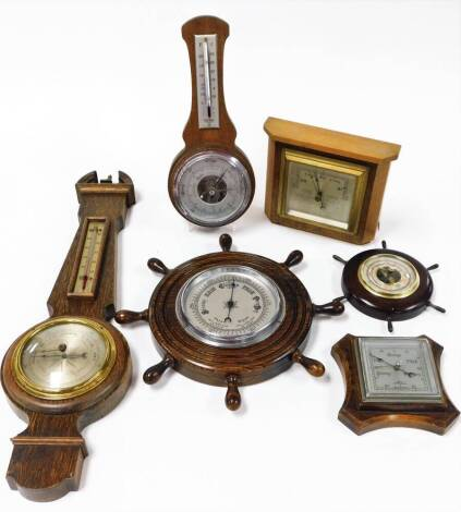 Various oak wall hanging barometers, ships wheel example, small banjo barometer with broken pediment and thermometer and barometer features, 54cm high, a shaped square example, etc. (a quantity)