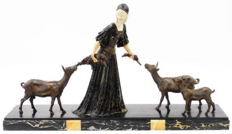 A Continental Art Deco bronzed and marble figure group, formed as a lady in flowing robes feeding goats, on a veined marble based, 49cm high.
