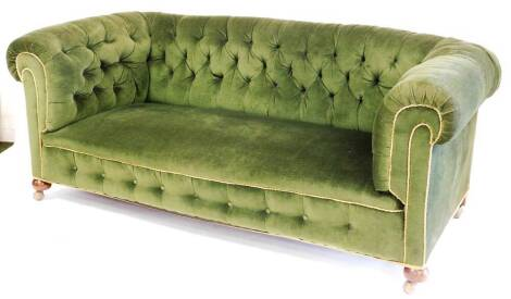 A Victorian button back Chesterfield sofa, with shaped arms, turned mahogany front bun legs terminating in castors, in later green material, 80cm high, 178cm wide, 91cm deep.