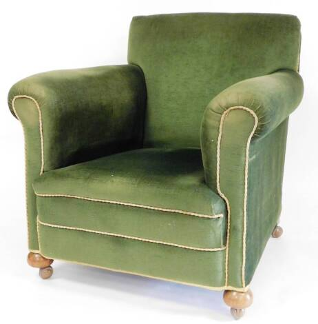 A Victorian mahogany framed armchair, with shaped back and arms, on bun feet, terminating in later castors, 85cm high.