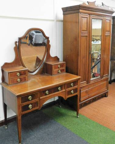 A matched Edwardian bedroom suite, comprising walnut wardrobe with single door, flanked by panels above drawer beneath, surmounted by a carved fixed cornice, 210cm, high, 113cm wide, 40cm deep, and an Edwardian mahogany and boxwood strung dressing table w