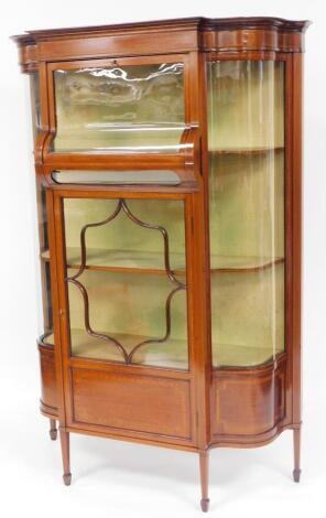 An unusual Edwardian mahogany serpentine and box wood display cabinet, with curved glass fall door to the upper compartment, flanked by further curved glass sections, above an astragal glazed floral section with lower panel, on square taper legs terminati