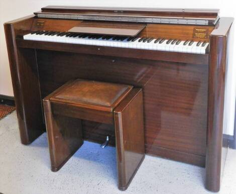 """An Eavestaff """"mini piano"""", in shaped Art Deco case, with articulated music rest, 92cm high, 142cm wide, 46cm deep, with leather topped stool."""