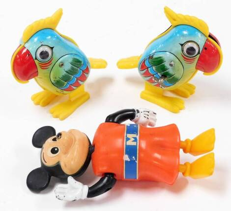 Two similar 1970's Yone Japanese plastic and tin plate parrot ornaments, one marked made in Singapore, 10cm high, and a clockwork plastic Walt Disney Mickey Mouse waving figure. (3)