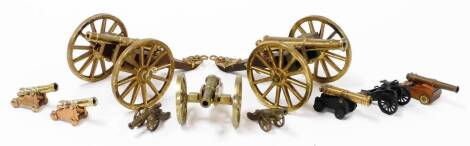 Various model brass table cannon, to include one on truckle wheeled base, 13cm wide, another similar, various others, etc. (a quantity)