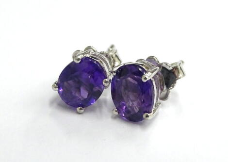 A pair of amethyst stud earrings, each with butterfly backs, in silver, 2.7g all in.