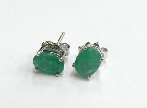 A pair of emerald stud earrings, each with butterfly backs, in silver, 2.6g all in.