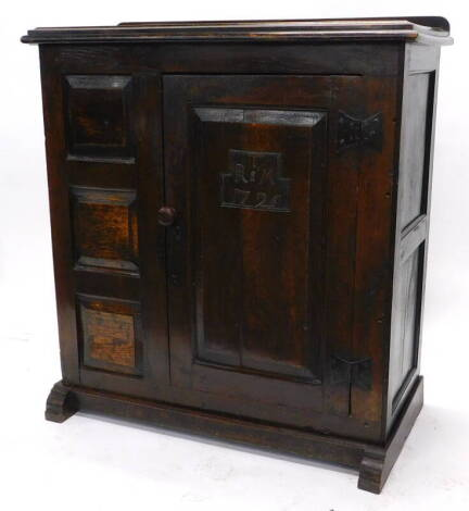 An early 18thC joined oak livery cupboard, the loose top with a moulded edge above a single panelled door bearing initials T above R&M and date 1726, flanked to one side with three panels, enclosing two shelves, on end supports, 117cm high, 110cm wide, 51