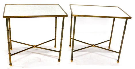 A pair of brass rectangular occasional tables, each with a mirrored top etched with Chinoiserie designs, on turned supports with 'x' shaped stretcher, 51cm high, 54cm wide, 39cm deep.