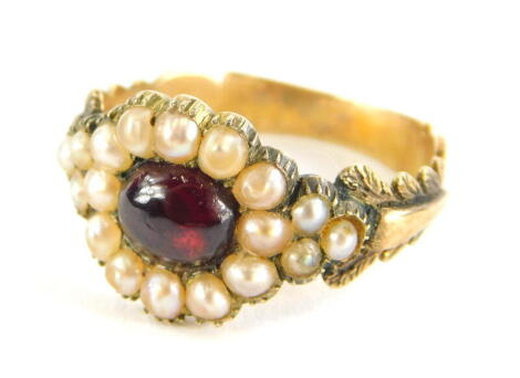 A Victorian memorial ring, set with cabochon garnet stone, surrounded by seed pearls, with scroll and acanthus leaf shoulders, inscribed A Memorial of Lasting Affection, yellow metal, unmarked, ring size P½, 3.6g all in.