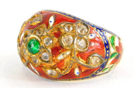 An Indian enamel and gem set ring, the ring set with central cabochon green emerald, in a floral cluster set with various old cut diamonds, in red, blue and white enamel, on a yellow metal band, unmarked, the enamel AF, ring size K½, 6.4g all in.