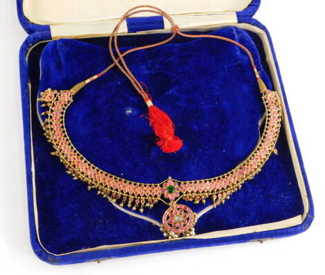An Indian dress necklace, the necklace set with cabochon set rubies, with emerald and moon stone centre, with cultured pearl pendant surround, on a plain gold coloured back, possibly silver gilt, on a red and gold string necklace, 22cm wide approx, 45.3g